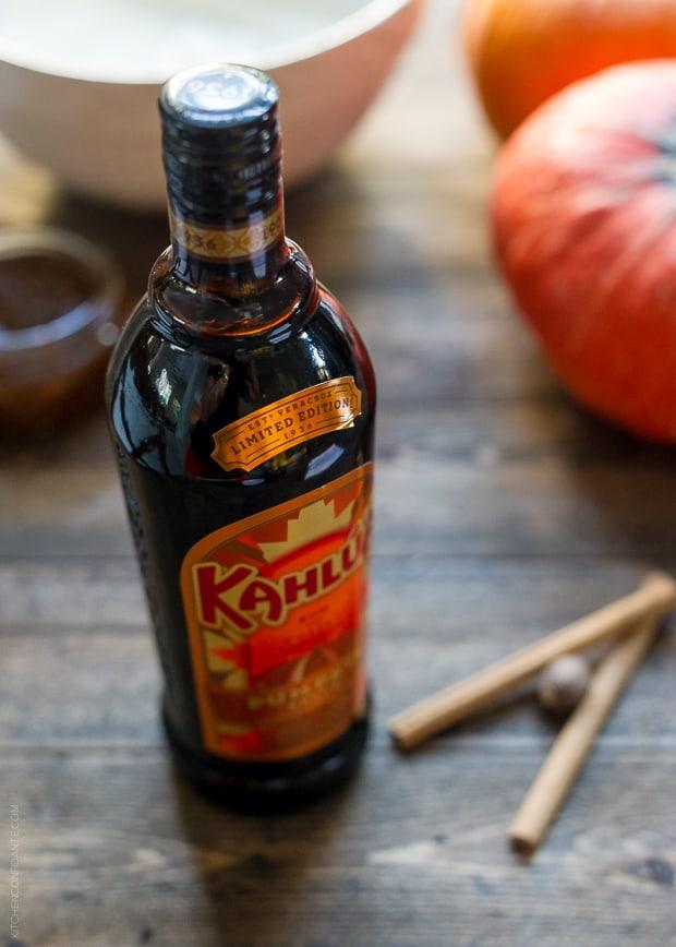 A bottle of Kahlúa Pumpkin Spice on a wooden surface.