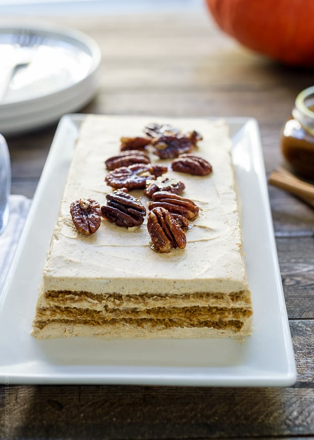 No Bake Pumpkin Spice Kahlúa Cheesecake served a on a white rectangular platter with candied pecans on top.