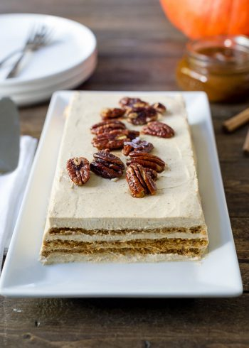 A No Bake Pumpkin Spice Kahlúa Cheesecake served a on a white rectangular platter with candied pecans on top.