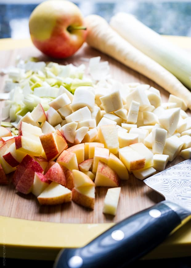 Chopped apples, parsnips, and leeks on a wooden surface.