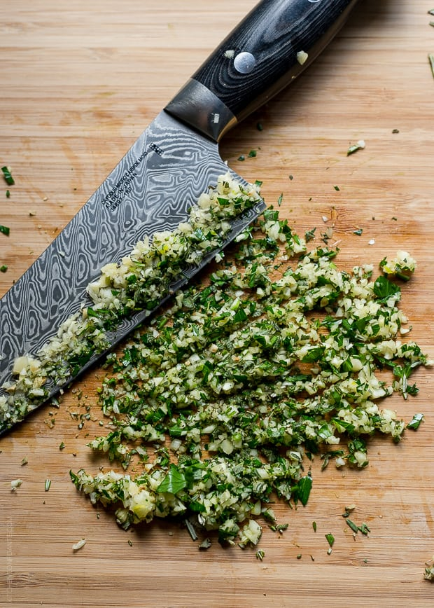 Garlic and fresh herbs chopped on a wooden surface.