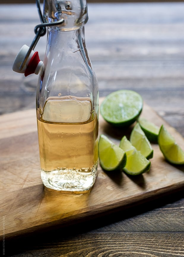 A glass bottle of ginger beer and slices of lime on a wooden surface.