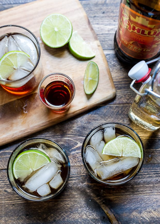 Cocktails on a wooden surface surrounded by a cutting board, slices of lime, ginger beer and Kahlúa Pumpkin Spice.