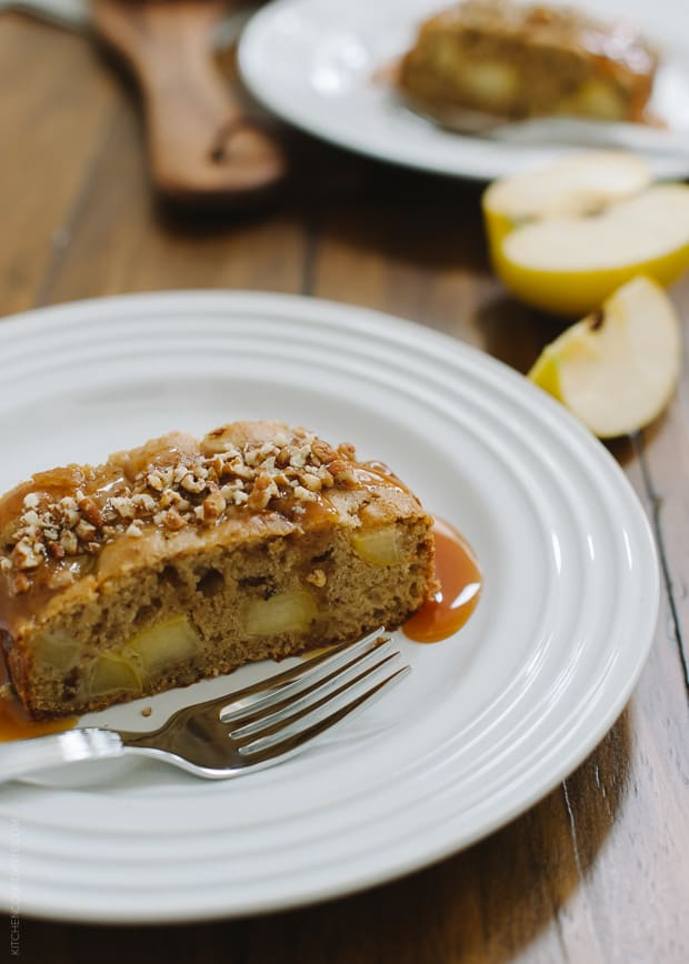 A slice of apple cake on a white plate with a fork.