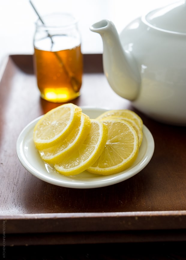 Lemon slices on a white plate with a teapot in the background.