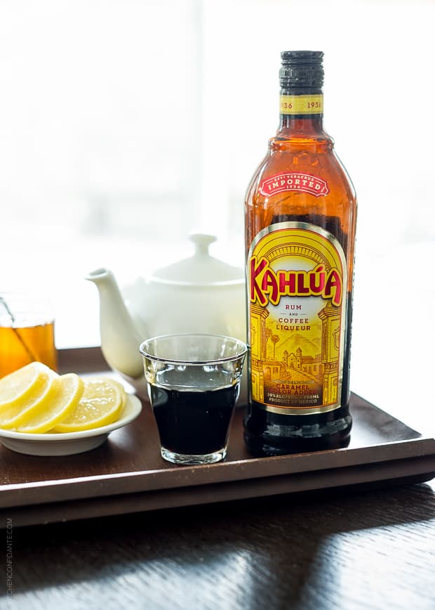 Kahlúa bottle on a tray with lemon slices and a teapot in the background.