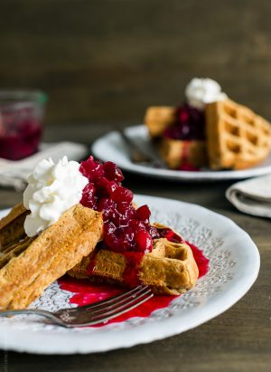 Gingerbread Belgian Waffles served on a white plate with cranberry compote and a whipped cream topping.