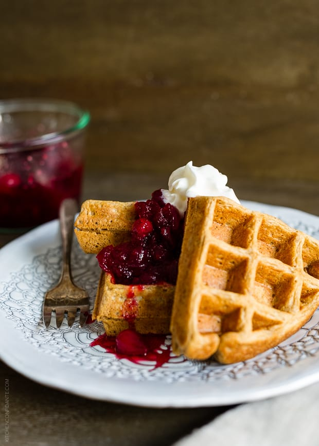 Gingerbread Belgian Waffles with a cranberry compote on a white plate.
