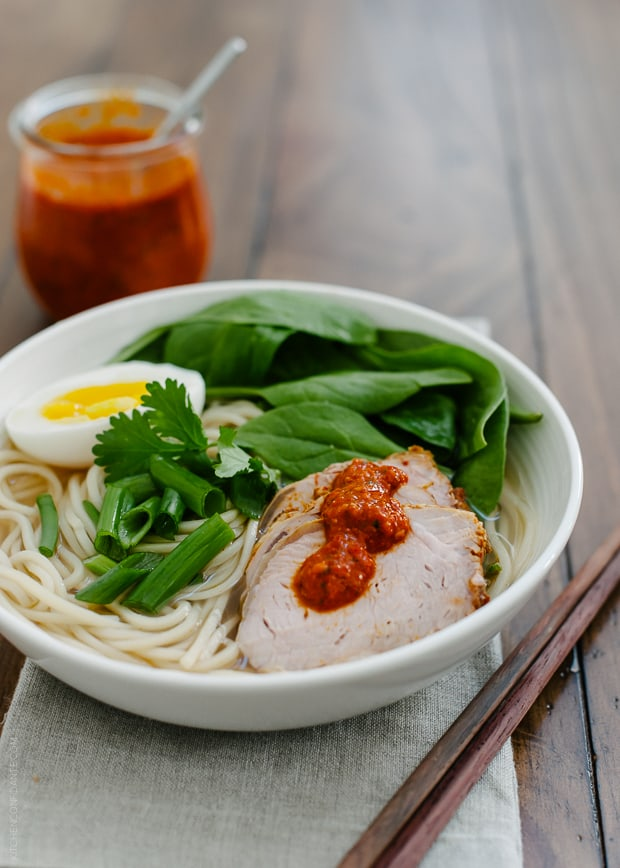 A bowl of Harissa Ramen topped with pork slices, a soft egg, spinach and harissa.