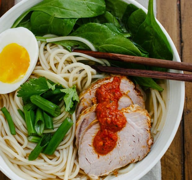 A bowl of ramen topped with pork slices, a soft egg and harissa.