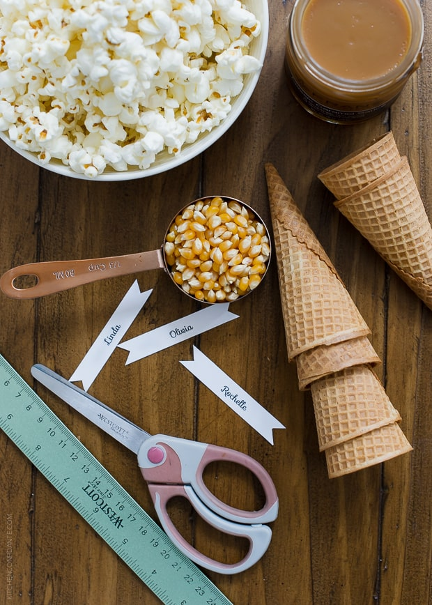 Supplies to make Popcorn Christmas Tree Place Cards including a scoop of popcorn, cardstock, scissors, ice cream cones and caramel.