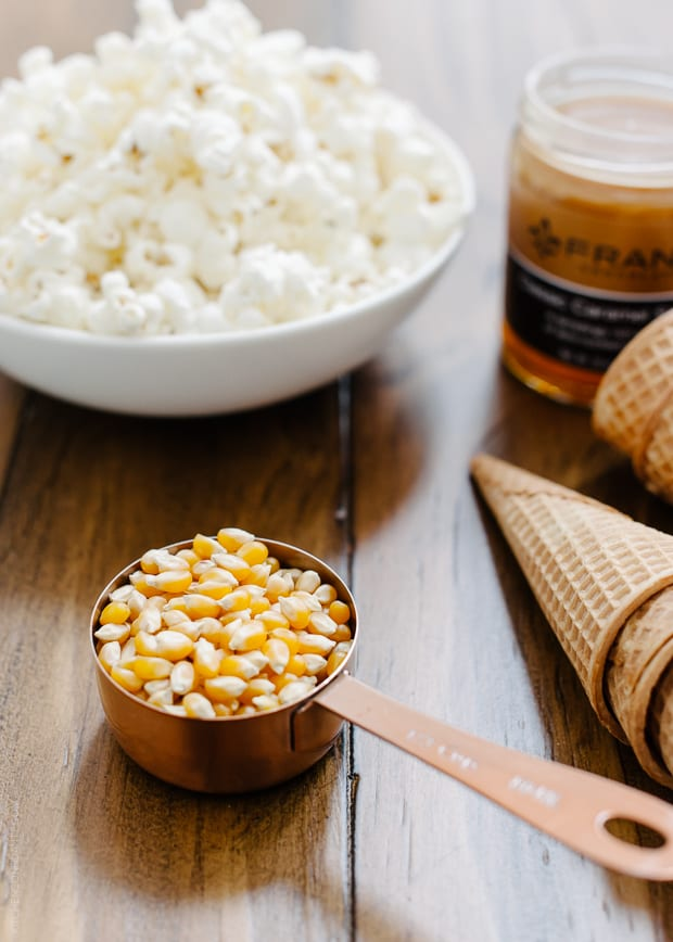 A scoop of popcorn kernels with popcorn in the background.