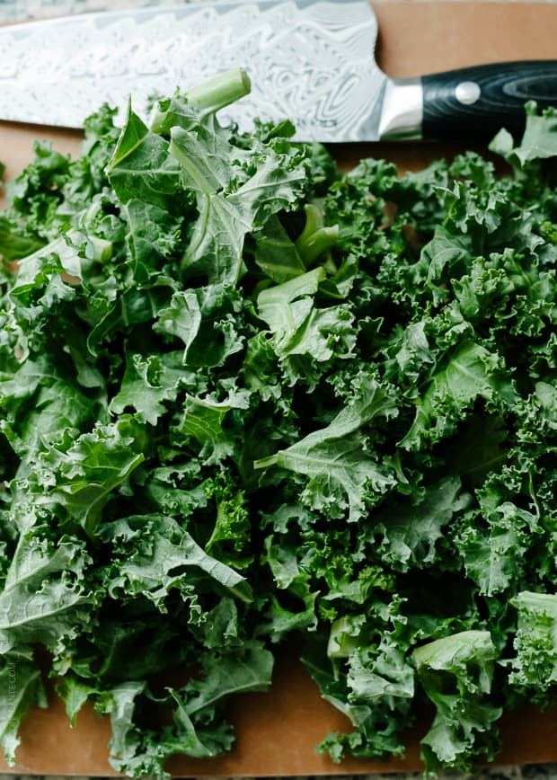 Kale on a cutting board for Sweet Potato and Kale Coconut Curry Soup.