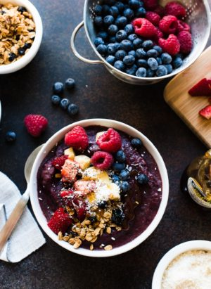 Acai Berry Bowl topped with bananas, granola, berries, coconut, chia seeds and honey.