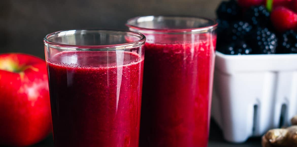 Soothing Hot Apple Berry Ginger Juice in glasses with fresh berries, apple and ginger.