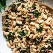 Swiss Chard with Orzo, Cannellini Beans and Pancetta in a white serving dish.