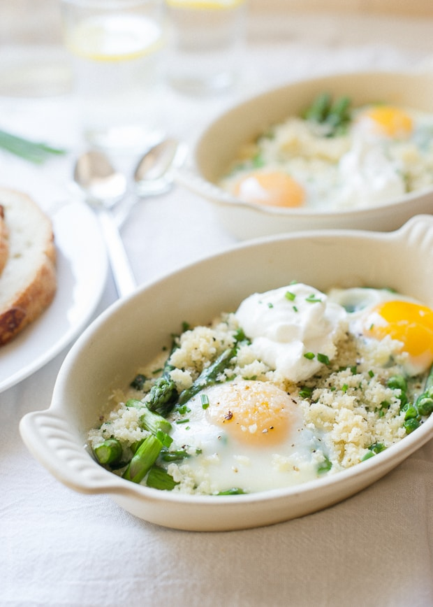 A small white ramekin filled with baked eggs, asparagus, and peas.