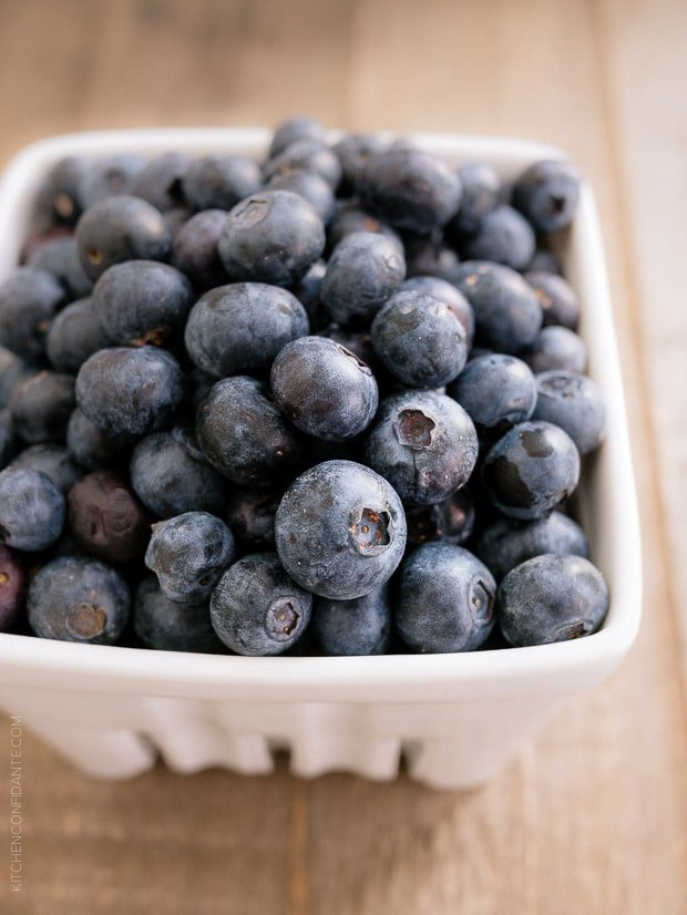 Fresh blueberries in a white container on a wooden surface.