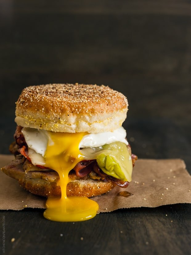 A Cubano Breakfast Sandwich made with an English Muffin and piled high with meat and a sunny side up egg.