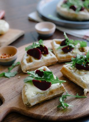 Waffle Pizzas with Roasted Garlic, Beets and Brie on a wooden serving board.