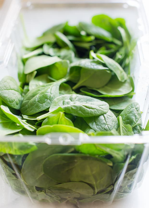 A clear plastic container of baby spinach for a Green Smoothie Bowl