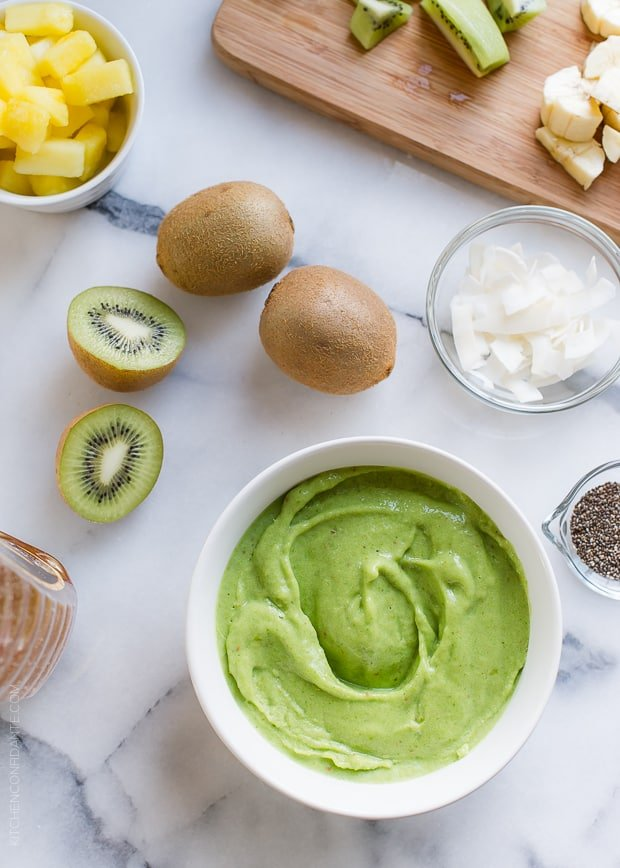 The base of a Green Smoothie Bowl with toppings such as kiwi and coconut on a marble board