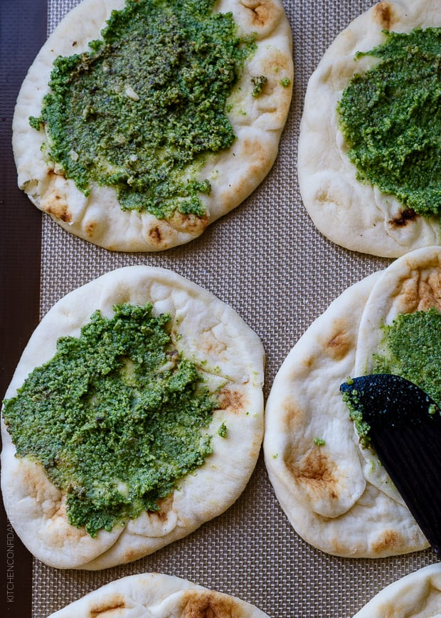 Mini naan spread with pesto on a baking sheet.