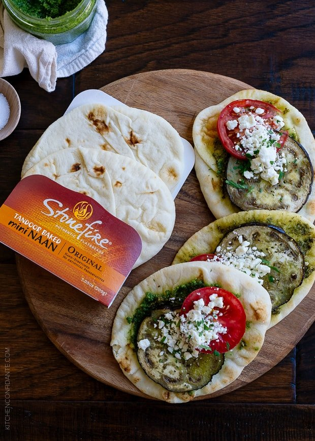 Roasted Eggplant, Tomato and Pesto Mini Naan on a wooden surface.