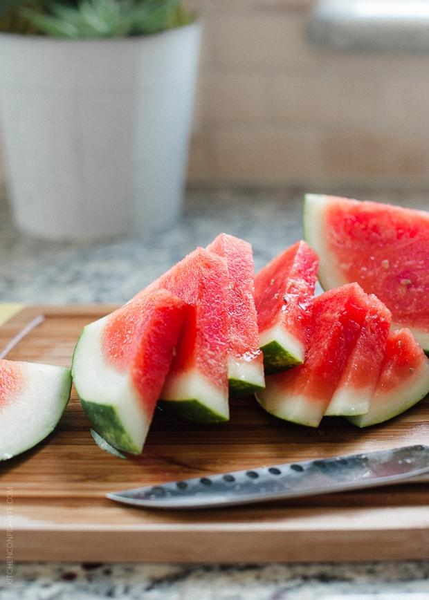 Fresh watermelon slices on a cutting board.