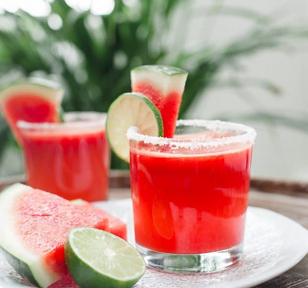 Watermelon Lime Margaritas garnished with slices of lime and watermelon.