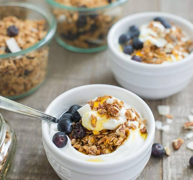 Blueberry Maple Granola served with yogurt and honey in a small white bowl.