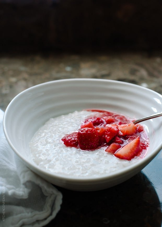 A white bowl of Coconut Tapioca Pudding with a spoonful of bright red Strawberry Rhubarb Compote on top.