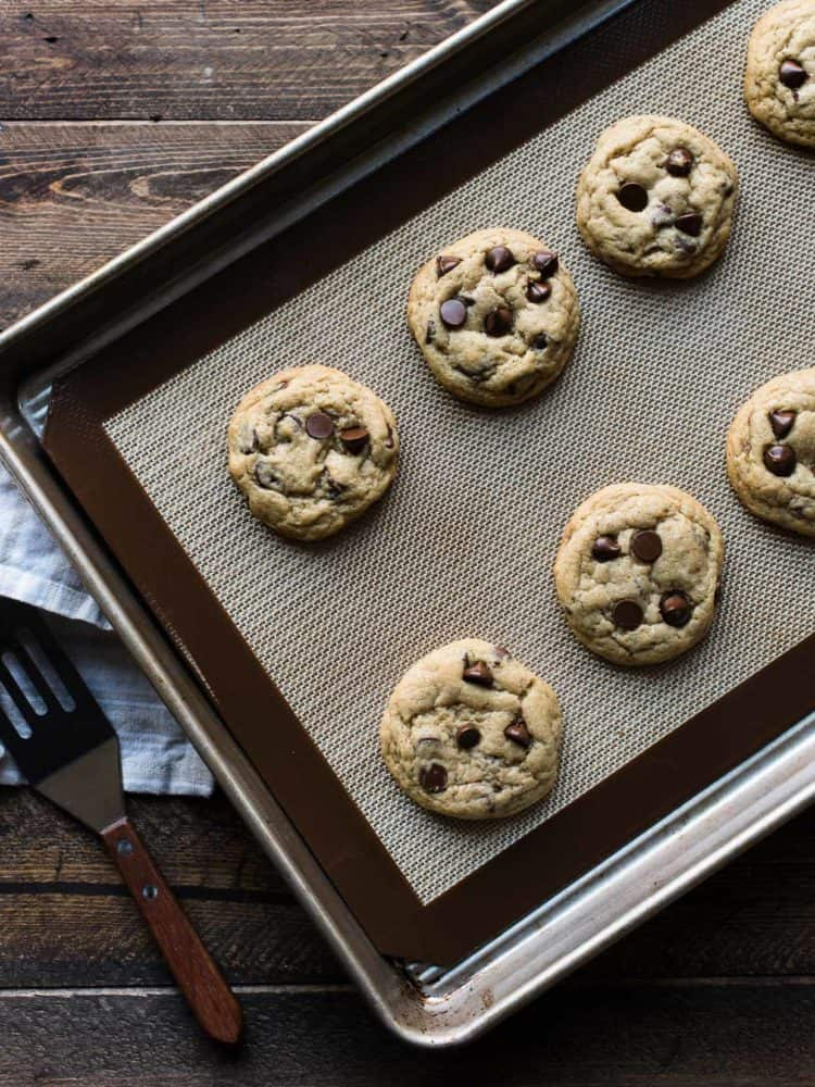 Freshly baked cookies with chocolate chips on a cookie sheet on a wooden table.