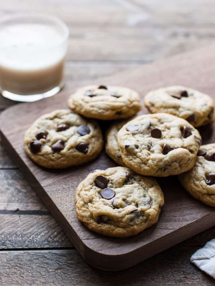 A pile of chocolate chip cookies on a wooden board with a glass of milk.