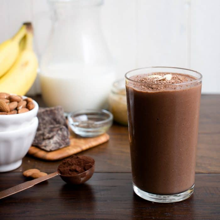 A Dark Chocolate Almond Butter Smoothie in a glass on a wooden surface.