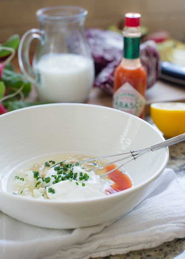Tabasco and other ingredients in a white bowl ready to stir together a buttermilk dressing.