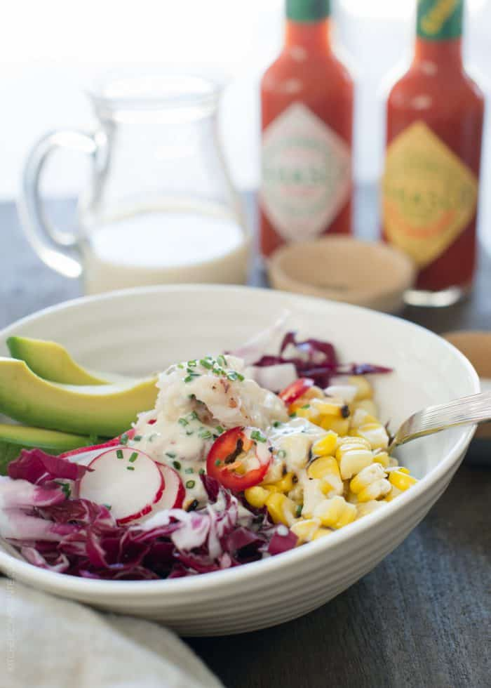 Dungeness Crab Salad in a white bowl garnished with radicchio, radishes, and sliced avocado.