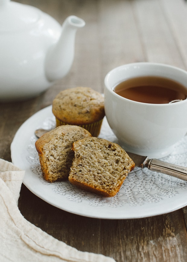 A Banana Nut Ricotta Muffin halved on a plate alongside a cup of tea.