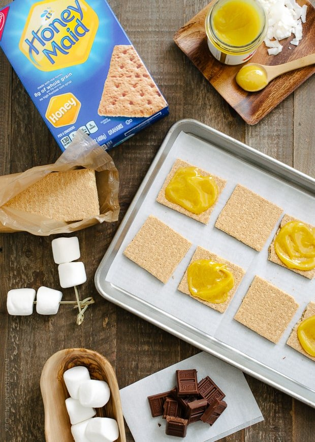 Graham crackers spread with coconut jam on a sheet pan.