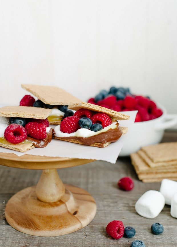 Homemade s'mores arranged on a wooden cake stand.