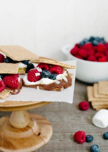 Coconut Jam Berry S'mores arranged on a wooden cake stand.