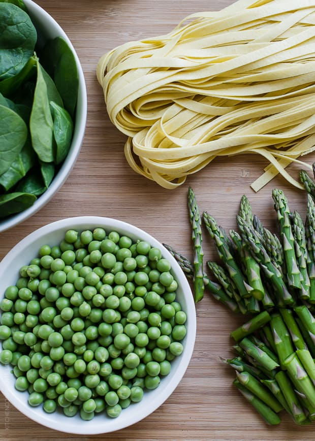 A bowl of spinach, a bowl of peas, chopped asparagus, and fresh fettuccine on a wooden surface.