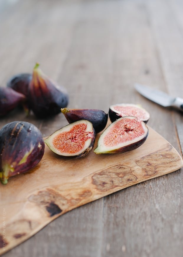 Fresh summer figs sliced on a wooden serving board.