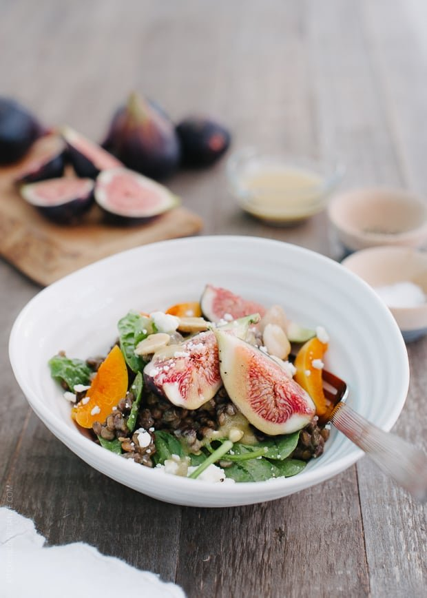 Fig and Apricot Summer Lentil Salad in a white bowl on a wooden surface.