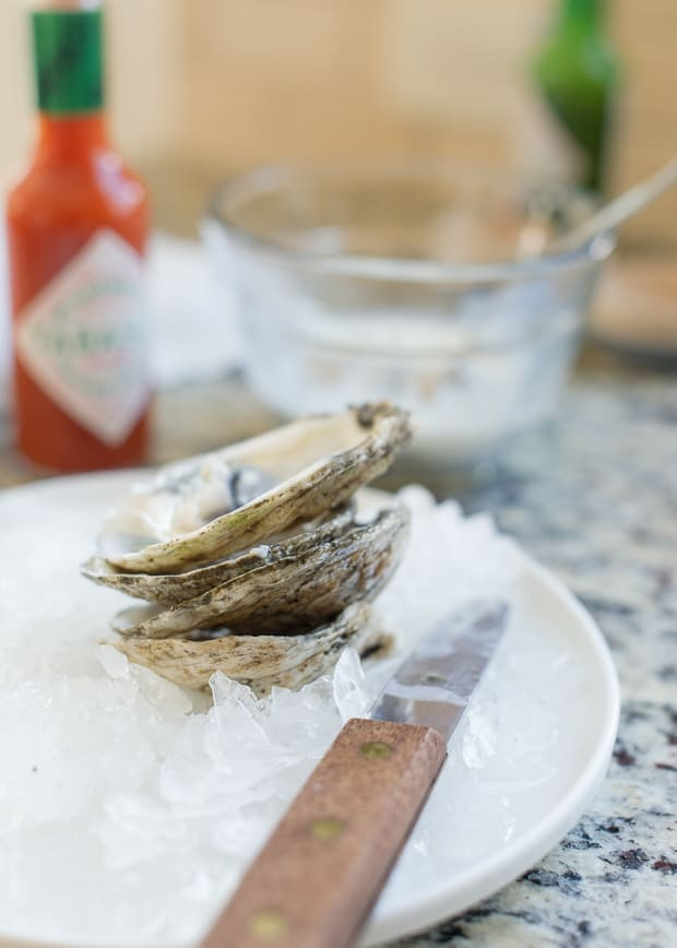 A small stack of fresh oysters on ice.