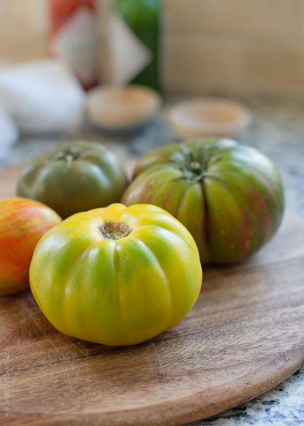 Red and green heirloom tomatoes on a wooden serving board.