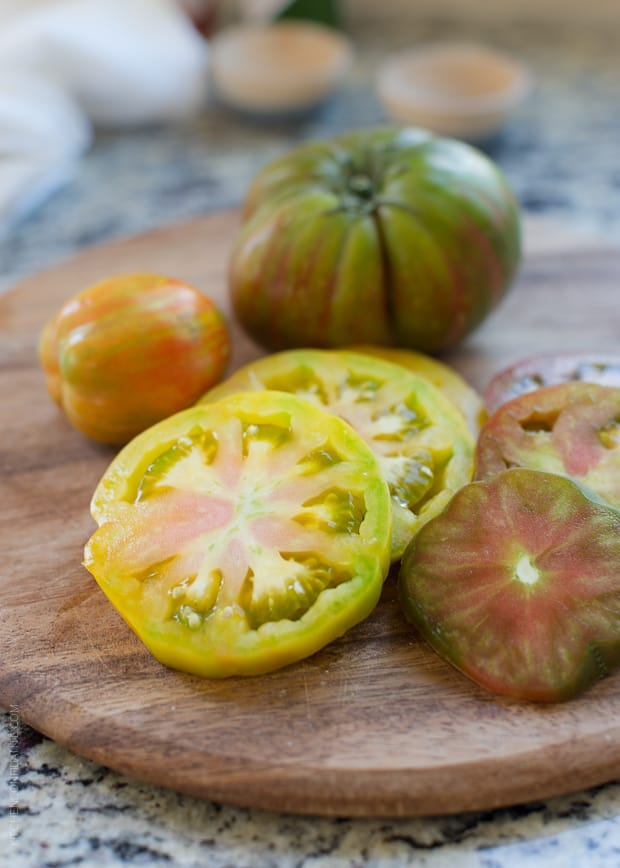 Slices of colorful heirloom tomatoes on a wooden serving board.