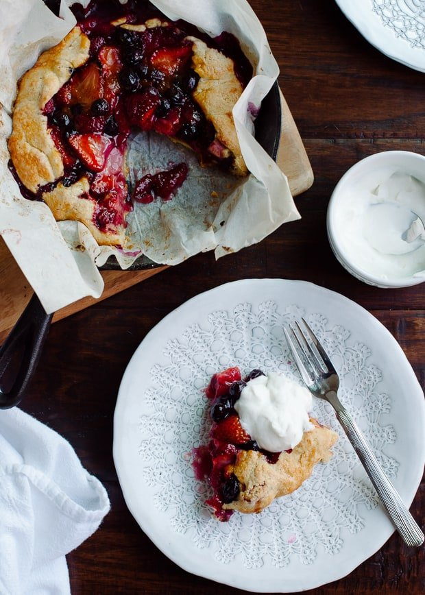 A slice of Mixed Berry Cornmeal Galette on a white plate with a dollop of whipped cream on top.