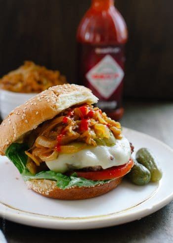 A hamburger loaded with toppings like cheese, tomato, pickles, and Sriracha Caramelized Onions.
