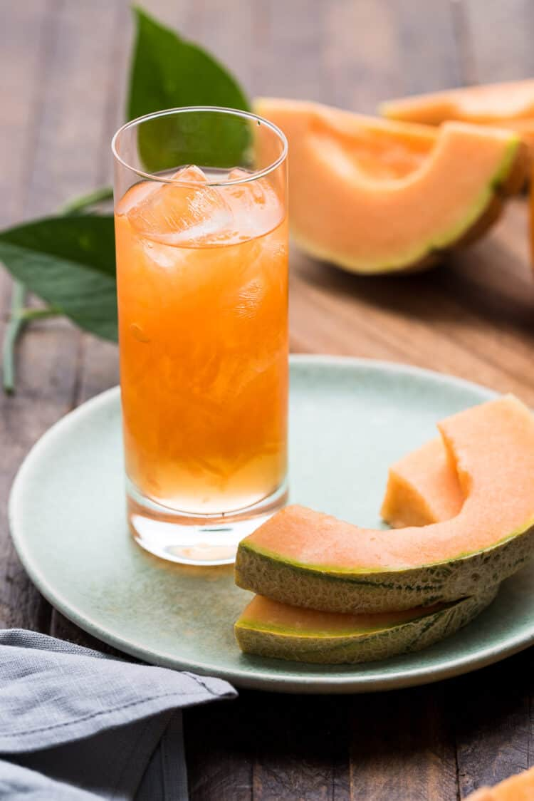 Cantaloupe Juice in a tall glass with slices of melon on a plate.